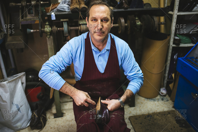 Portrait of shoemaker sewing a shoe in his workshop