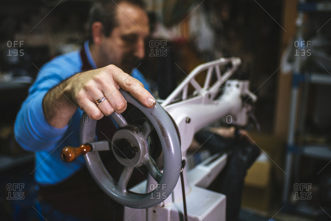 Shoemaker using a sewing machine in his workshop, close-up