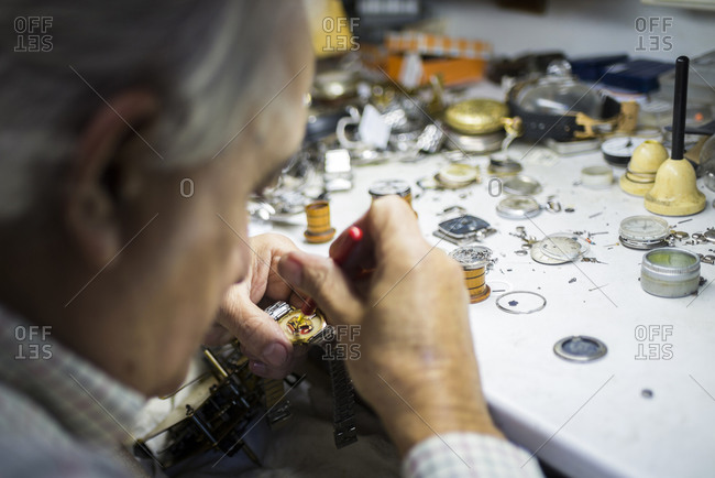 Watchmaker in foreground while working with a wristwatch
