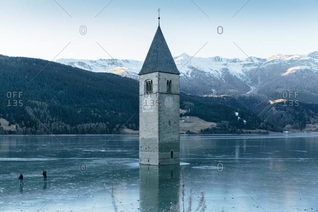 Italy, Venosta Valley, Sunken spire in frozen Lago di Resia