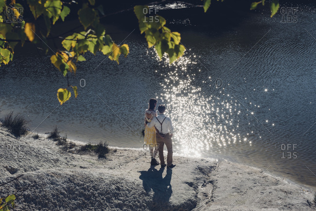 Back view of lovers standing at water edge