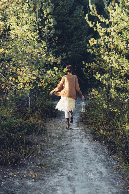 Back view of old-fashioned styled woman with storm lamp walking on a path