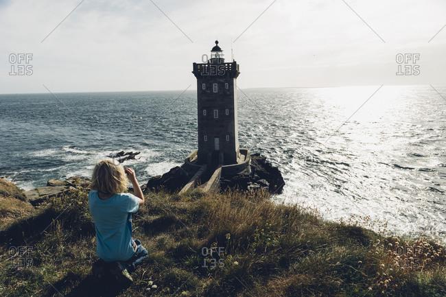 France, Brittany, Pointe de Kermorvan, Le Conquet, boy at lighthouse Phare de Kermorvan
