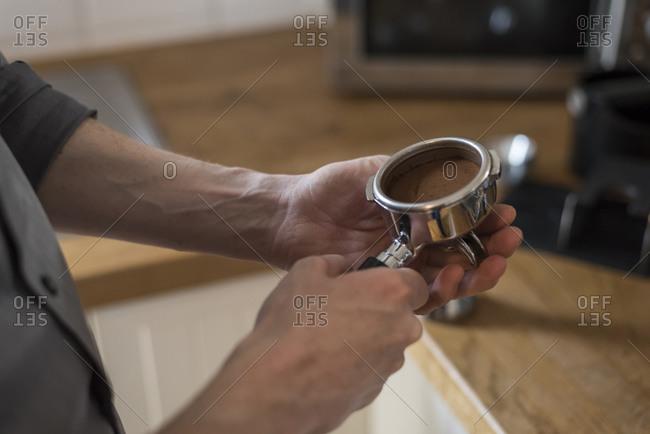 Preparing a cappuccino, coffee filter, pressed coffee powder in portafilter
