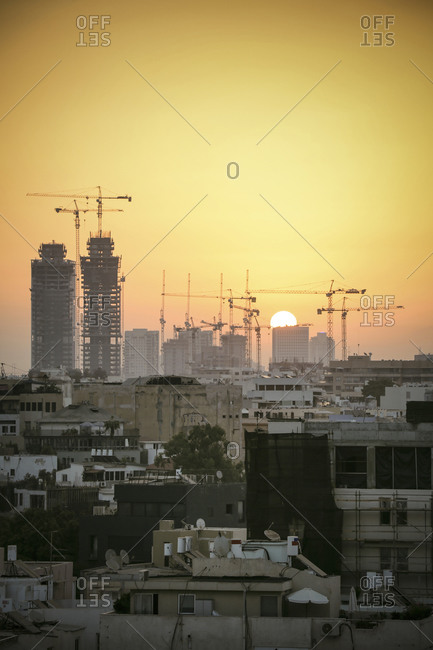 Israel, Tel Aviv, cityscape with cranes at sunset