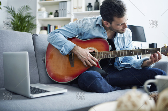 Young man at home sitting on couch playing guitar next to laptop