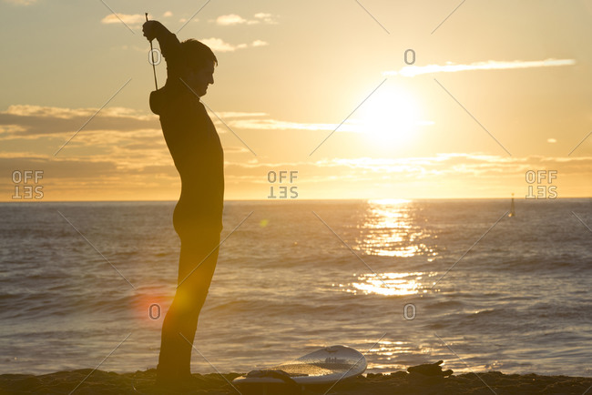 Surfer at sunrise on the beach