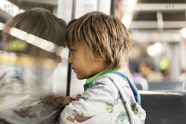 Little boy looking through window of a subway train