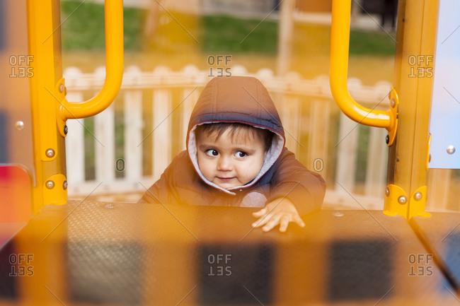 Portrait of little boy climbing on playground equipment