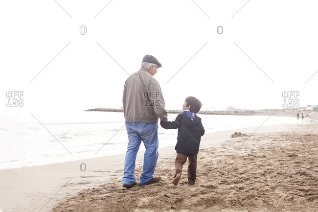Grandfather and grandson walking and talking on the beach