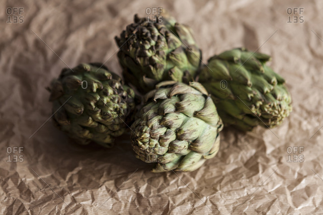 Four artichokes on crumpled brown paper