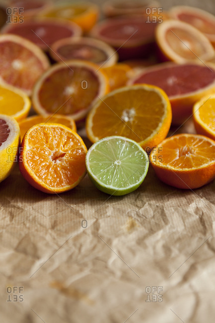 Halves of different citrus fruits on crumpled brown paper