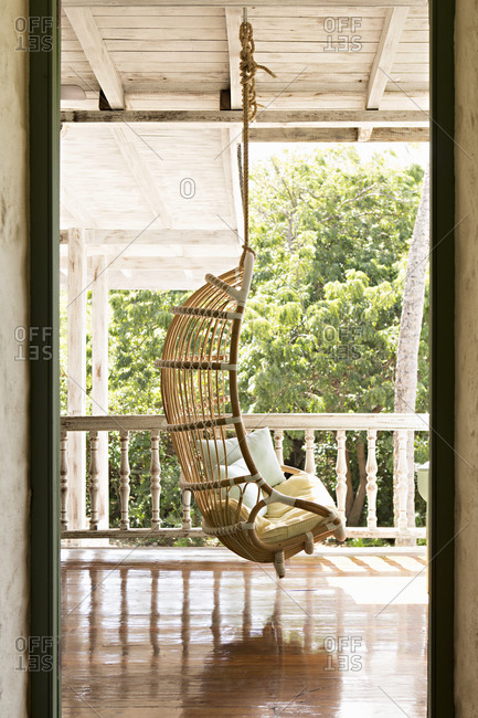 Mustique, Mustique Island, St Vincent and Grenadines - January 20, 2016: Hanging rattan chair on a covered porch at the Cotton House hotel