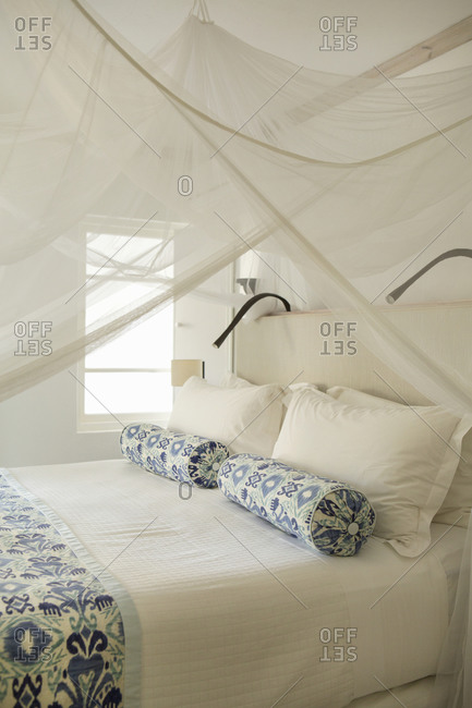 Bedroom in a resort with blue patterned pillows and canopy