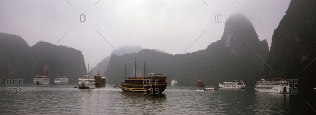 Ha Long Bay, Vietnam - August 13, 2012: Boats in mist, Ha Long Bay, Vietnam