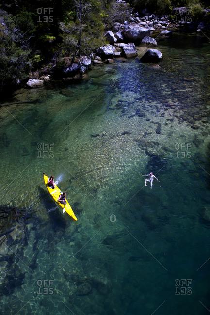 Kayakers swimming in river