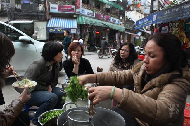 Hanoi, Vietnam - March 9, 2012: Eating street food in Hanoi, Vietnam