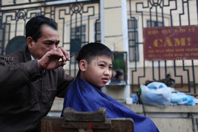Hanoi, Vietnam - March 9, 2012: Boy getting haircut, Hanoi, Vietnam