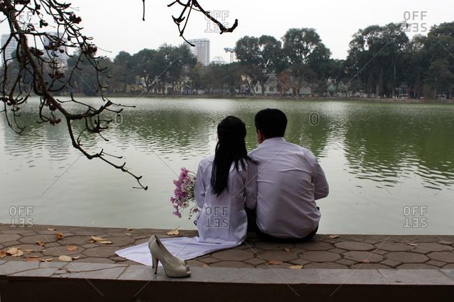 Married couple by lake, Hanoi, Vietnam