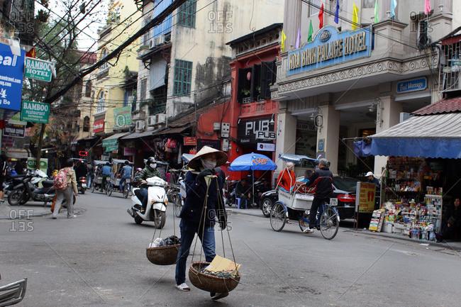 Hanoi, Vietnam - March 10, 2012: Woman carrying baskets, Hanoi, Vietnam