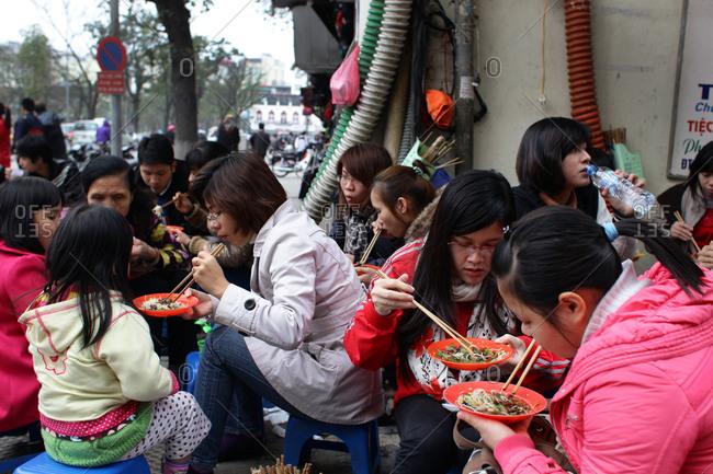 Hanoi, Vietnam - March 10, 2012: Locals eat on street corner, Hanoi, Vietnam