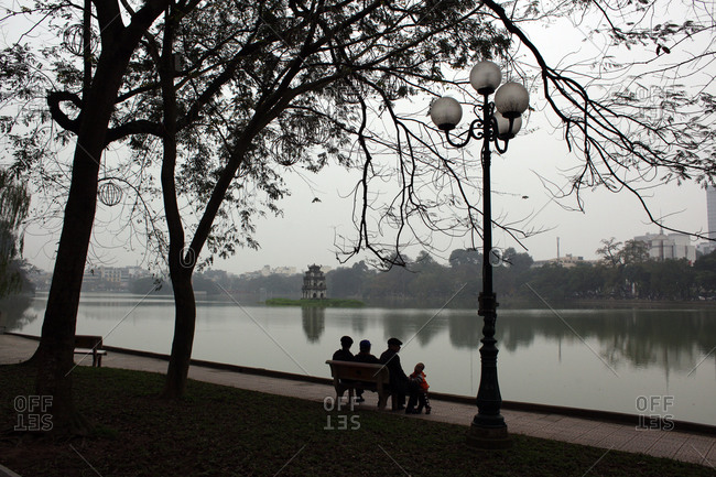 Hanoi, Vietnam - March 14, 2012: Family by lake, Hanoi, Vietnam