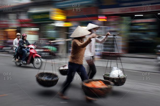 Hanoi, Vietnam - March 18, 2012: Locals carrying wares in Hanoi, Vietnam