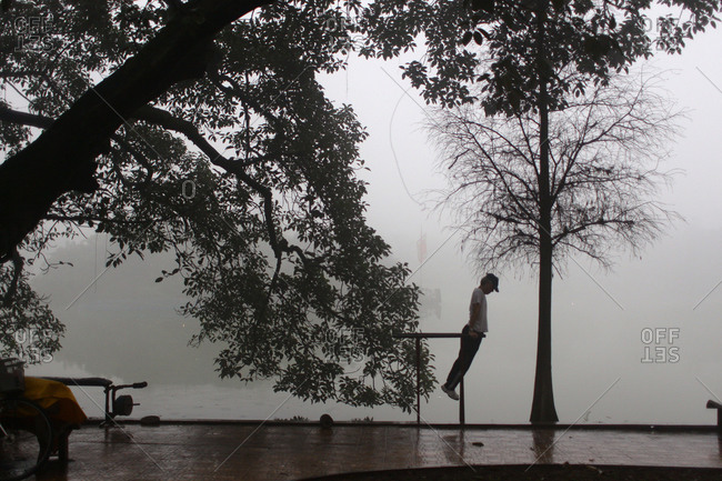 Hanoi, Vietnam - March 17, 2012: Man doing exercise by lake, Vietnam