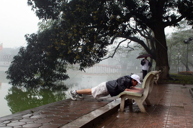Hanoi, Vietnam - March 17, 2012: Man using bench to exercise, Vietnam