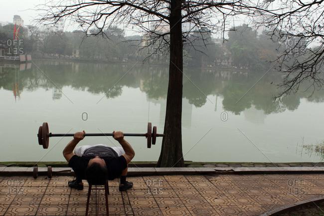 Hanoi, Vietnam - March 18, 2012: Man doing bench presses by lake