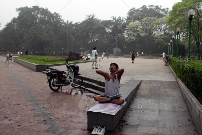 Hanoi, Vietnam - March 18, 2012: Man stretches in park, Hanoi, Vietnam