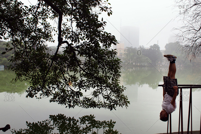 Hanoi, Vietnam - March 18, 2012: Man doing exercise by a lake