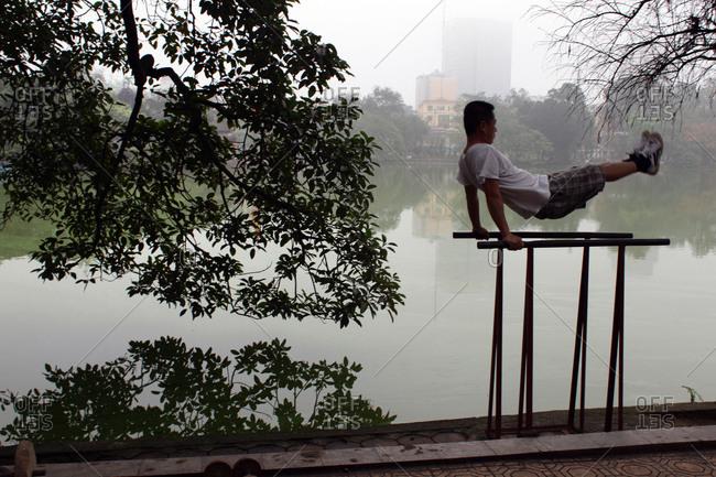 Hanoi, Vietnam - March 18, 2012: Man doing exercise by lake