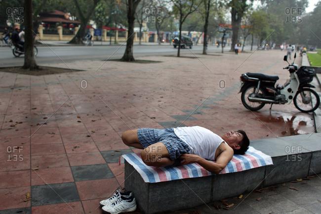 Hanoi, Vietnam - March 18, 2012: Man stretches in a park, Hanoi, Vietnam