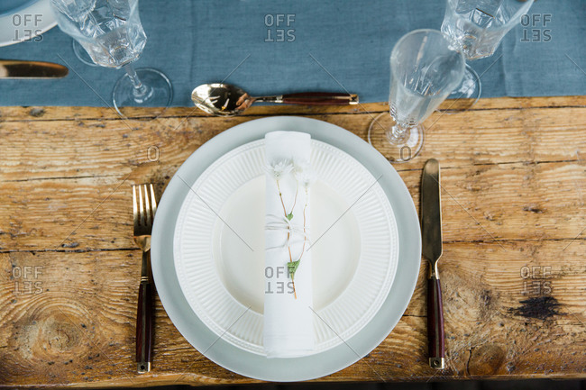 Overhead view of a blue and white place setting on a rustic wooden table