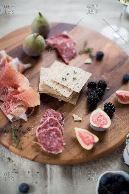 Crackers served with cured meats, figs, and berries