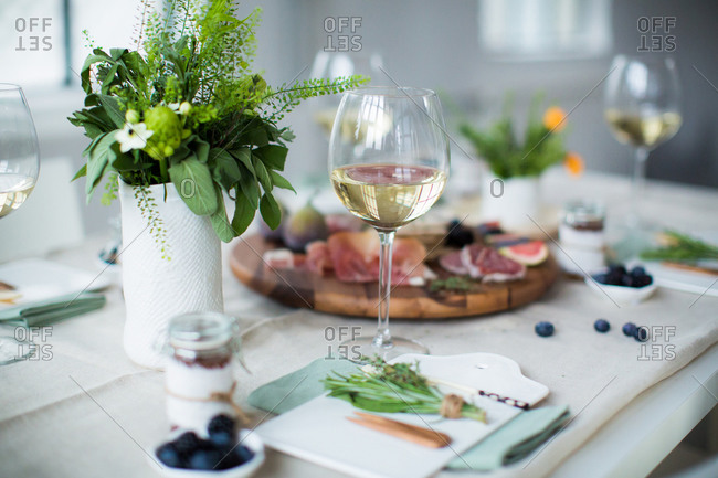 Glasses of wine with herb centerpiece and serving trays