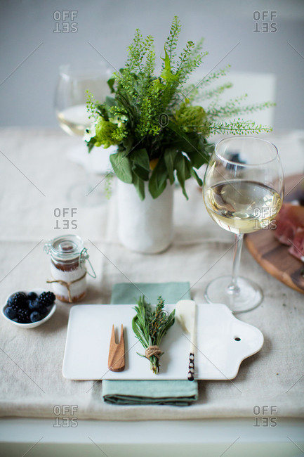 Place setting with glasses of wine and herbal centerpiece