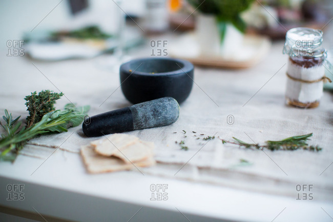 Mortar and pestle with fresh herbs on dining table
