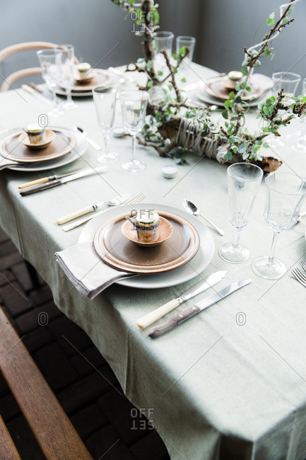 Dining table place setting with natural linens and rustic brown pottery plates