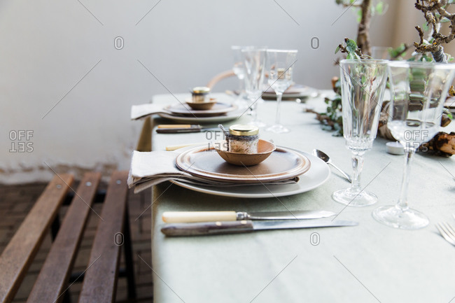 Natural dining table place settings with small jars of herbed salt