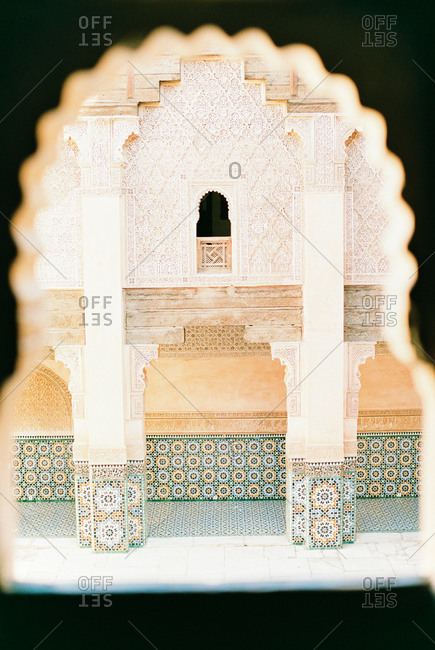 View through scalloped window opening of decorative tiles on building in Marrakech