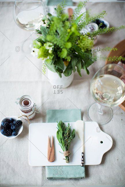 Overhead view of place settings with fresh herbs on a platter and glasses of white wine