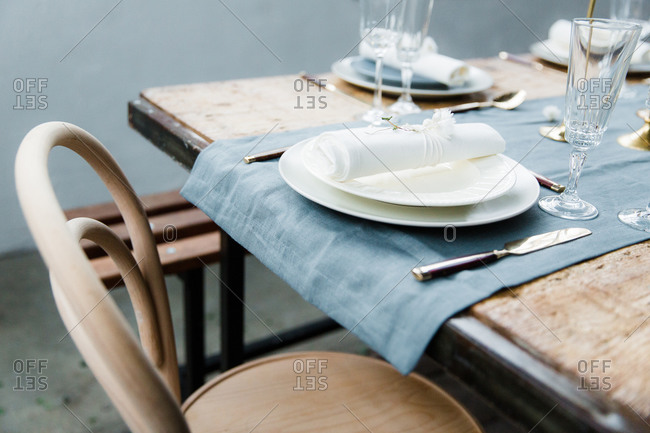 Wooden chair and table with blue linen runner and cream coloured plates