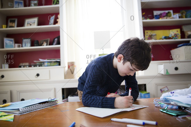 Boy writing on a piece of paper with a red marker