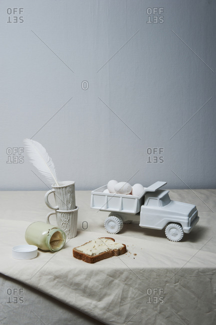 Still life with painted toy truck with eggs in white
