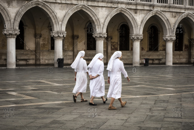 Venice, Italy - July 8, 2015: Three nuns walking in unison at the Piazza San Marco, Venice
