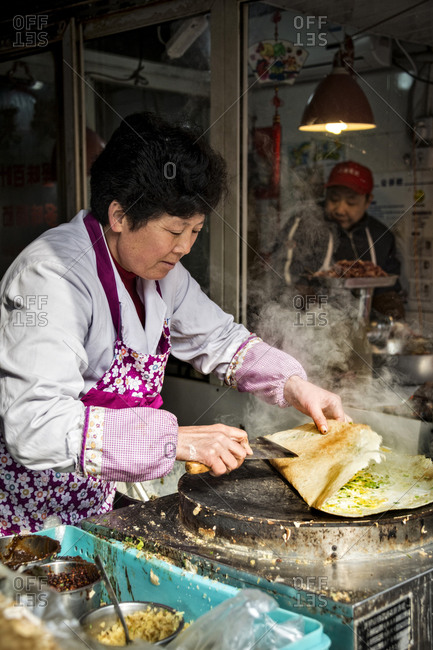 Shanghai, China - December 21, 2014: Woman frying a burrito, Shanghai