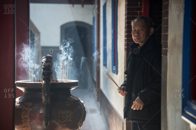 Taiwan - December 20, 2014: Taiwanese man standing with incense in his hands