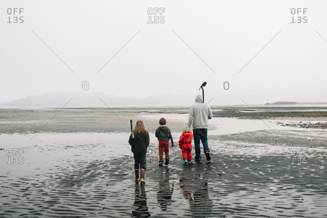 Father and his children walking across a beach to dig for clams